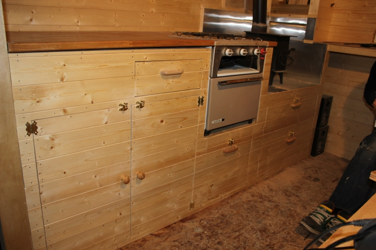 A beautiful pine kitchen! Alex followed the grain of the wood throughout the front of the kitchen units. Extra special attention to detail. Work surface from gumtree. Drawers at the end for our clothes and our little wood burner installed.